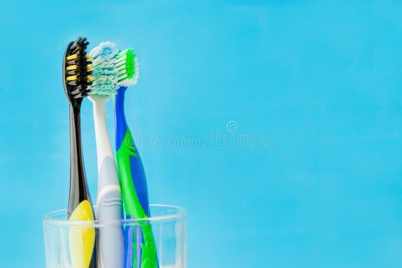 Комплект зубных щеток в стекле на голубой предпосылке Выбор зубной щетки концепции, космос экземпляра стоковое фото