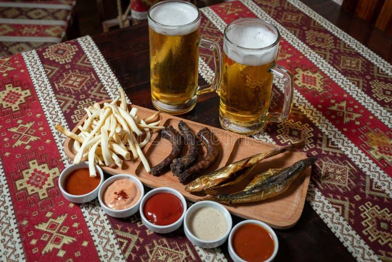 Комплект пива 2 пив и закуски на деревянной плите с 5 соусами На деревянном столе со скатертью с национальными картинами стоковые фотографии rf