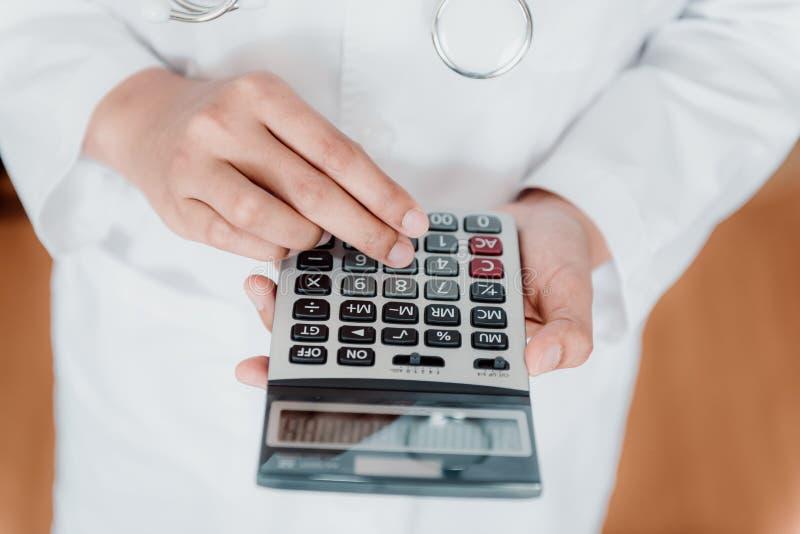 Конец-Вверх женского доктора высчитывает цену медицины в больнице офиса, женское медицинское использует калькулятор здравоохранен стоковое фото