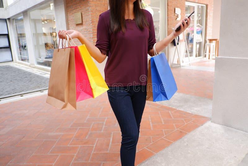 Конец-вверх женщины используя ее смартфон во время покупок стоковое фото