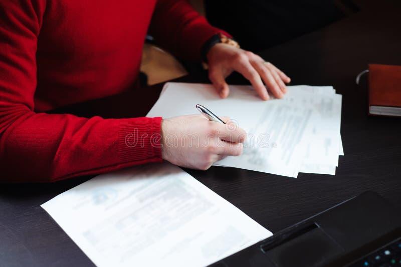 Конец-вверх мужских рук с ручкой над документом стоковые изображения