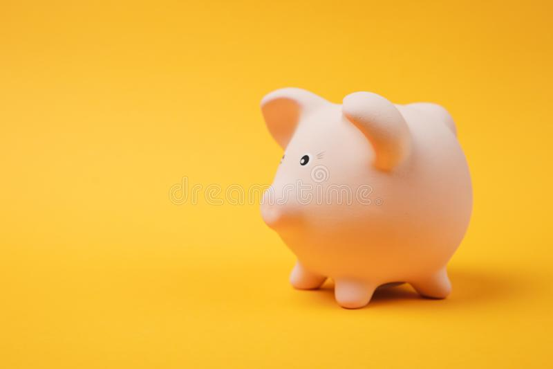 Конец вверх по фото, взгляд со стороны розового piggy банка денег на яркой желтой предпосылке стены Накопление денег стоковые изображения