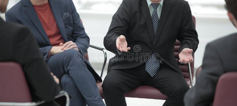 конец вверх деловые партнеры обсуждая сроки действия договора говорить встречи компьтер-книжки стола cmputer бизнесмена дела сь к стоковые изображения