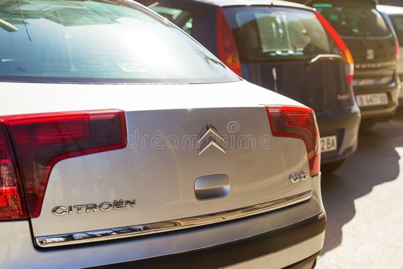 Конец-вверх светов логотипа и кабеля Citroen на заднем клобуке серебряного автомобиля припаркованного на улице города на солнечны стоковое изображение