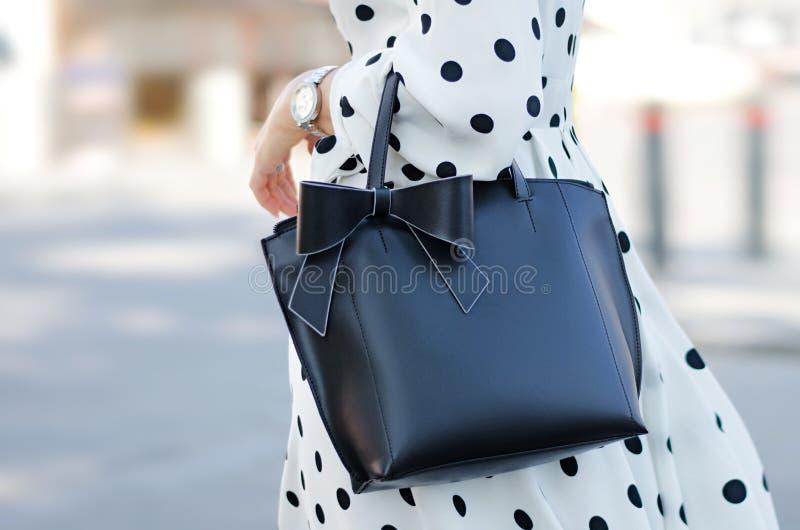 Конец-вверх сумки в женских руках Черно-белый стиль изображения Девушка в платье лета с точками польки и черной сумке со смычком  стоковая фотография