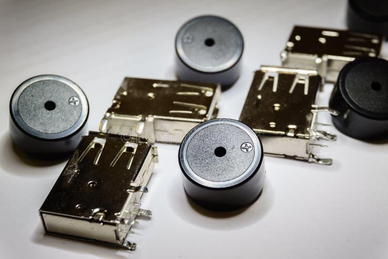 Конец-вверх разбросанных компонентов электроники гнезда и зуммера USB на белой предпосылке в частично фокусе и случайной картине стоковые фотографии rf