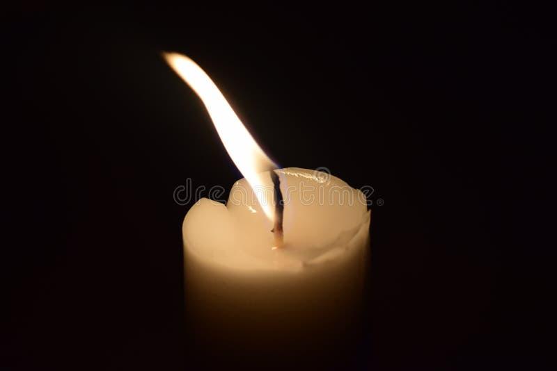 Конец пламени света свечи вверх с черной предпосылкой стоковая фотография