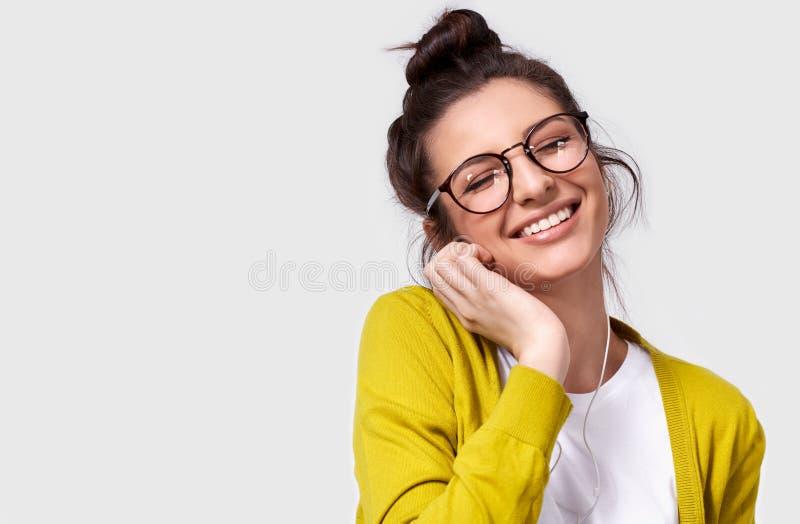 Конец студии горизонтальный вверх по портрету беспристрастной усмехаясь женщины в eyeglasses касаясь наушникам стоковое изображение