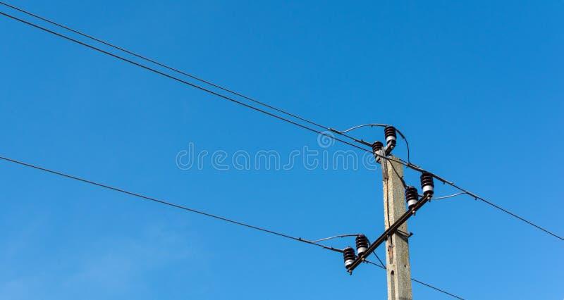 Конкретные электрические опора или столб с электрическими проводами против ясного голубого неба стоковые изображения