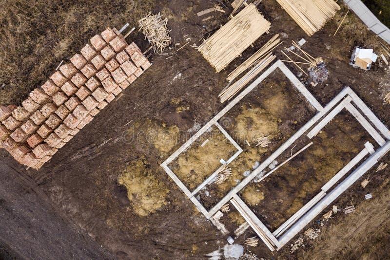 Конкретное учреждение для подвала будущего дома, стогов кирпичей и журналов тимберса здания для конструкции на солнечный летний д стоковая фотография