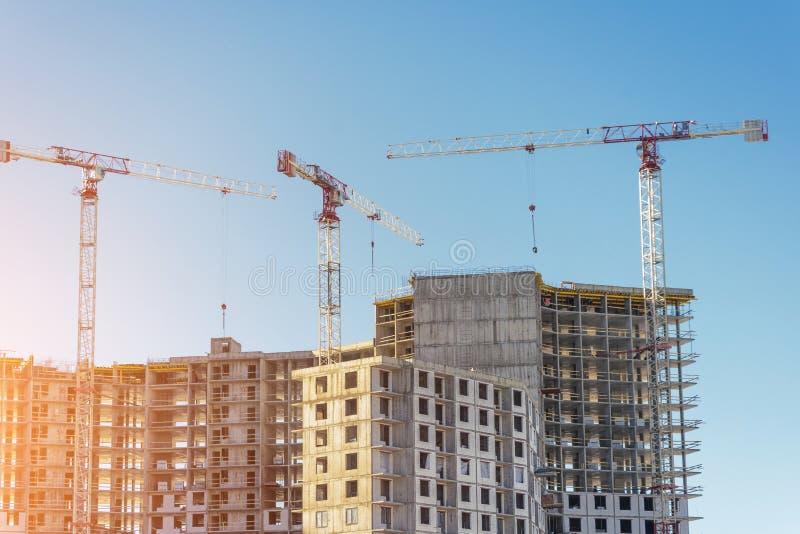 Конструкция жилой недвижимости их твердых бетона и кирпичей Взгляд домов и кранов высотного здания стоковое изображение