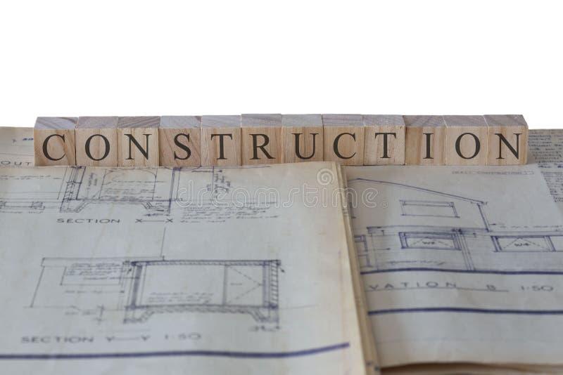 Конструкция написанная на деревянных блоках на светокопиях планов здания расширения дома стоковое фото