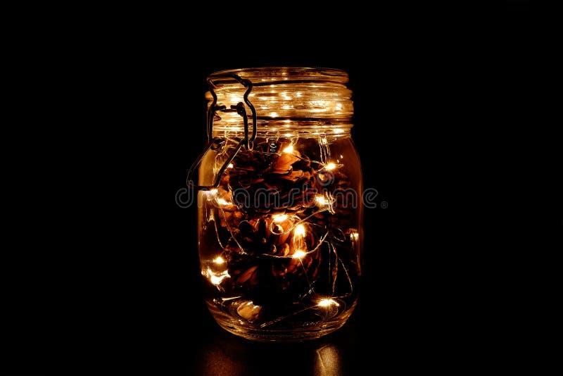 Конусы сосны со светом феи в опарнике каменщика стоковые фотографии rf
