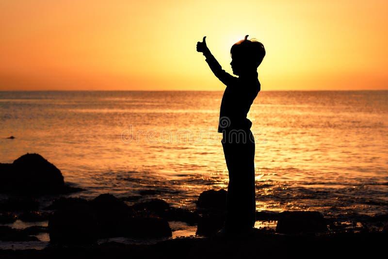 Контур мальчика с большими пальцами руки поднятыми на заходе солнца восхода солнца на seashore стоковое фото rf