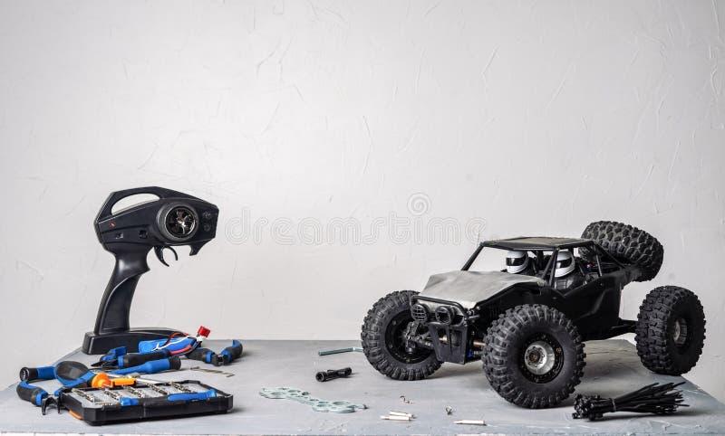 контролируемые Радио модели автомобиля: таблица с разбросанными инструментами для ремонтировать модели rc дефектные и пульт управ стоковое изображение rf