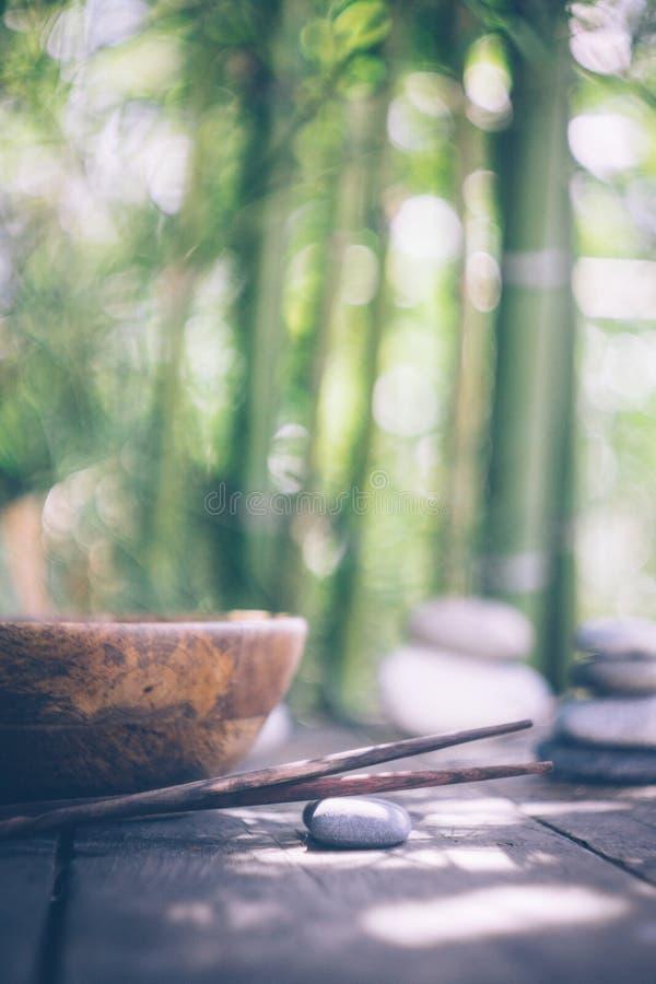 Концепция еды вытрезвителя: пустой деревянный шар, деревянные палочки, бамбук, камни на старом деревянном столе стоковые фото