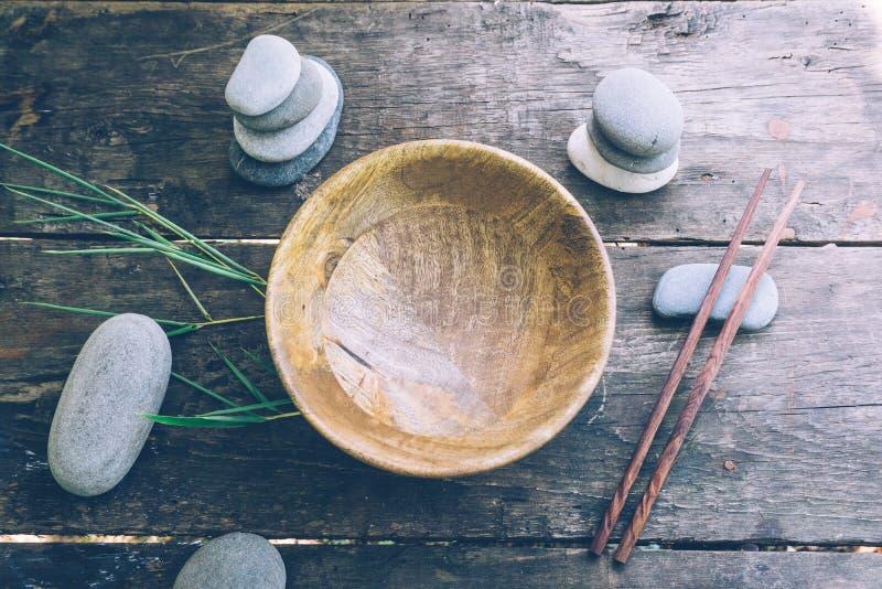 Концепция еды вытрезвителя: пустой деревянный шар, деревянные палочки, бамбук, камни на старом деревянном столе стоковые изображения