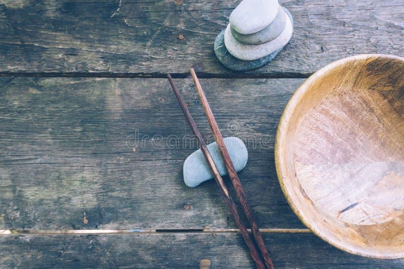 Концепция еды вытрезвителя: пустой деревянный шар, деревянные палочки, бамбук, камни на старом деревянном столе стоковое фото
