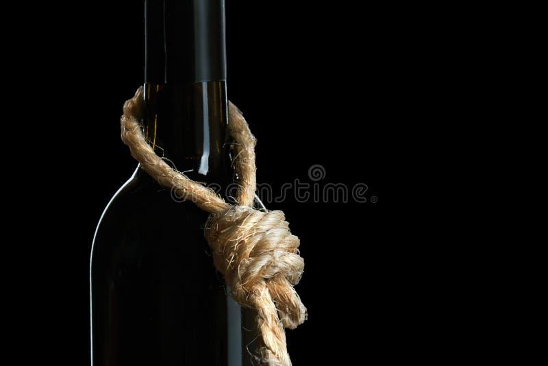 Концепция злоупотребления алкоголем Бутылка лозы с петлей веревочки на шеи символизирует что алкоголизм суицид стоковые изображения rf