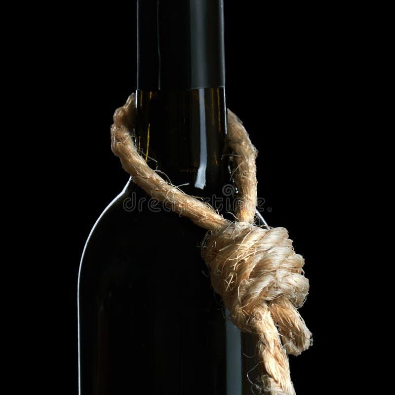 Концепция злоупотребления алкоголем Бутылка лозы с петлей веревочки на шеи символизирует что алкоголизм суицид стоковое фото rf