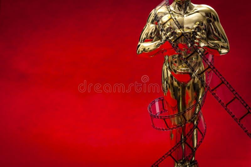 Концепция наград фильма Голливуд с сияющей металлической наградой фильма в оболочке в прокладке фильма целлулоида на красном ковр стоковые фотографии rf
