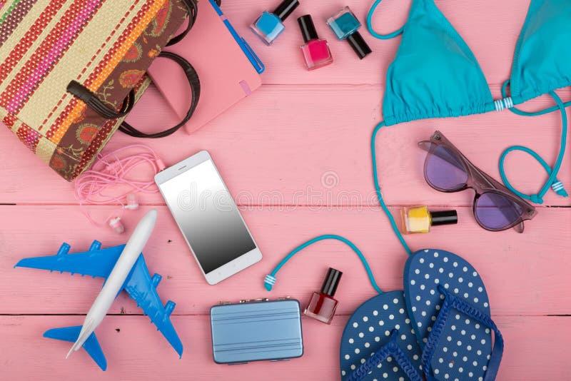 Концепция перемещения - лето women' мода s с голубым купальником, солнечными очками, умным телефоном, темповыми сальто сальт стоковая фотография rf