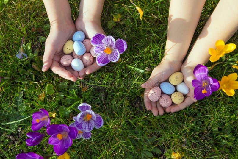 Концепция праздников пасхи Дети ищут и находят пасхальные яйца стоковые фото