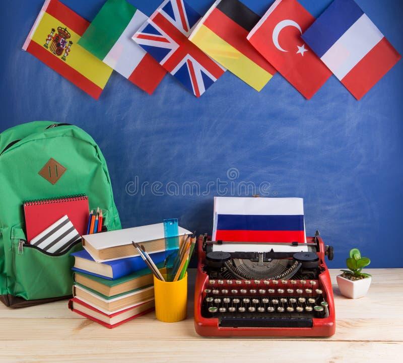 Концепция политических, новостей и образования - красная машинка, флаг России и другие страны, рюкзак, книги, канцелярские принад стоковые изображения rf