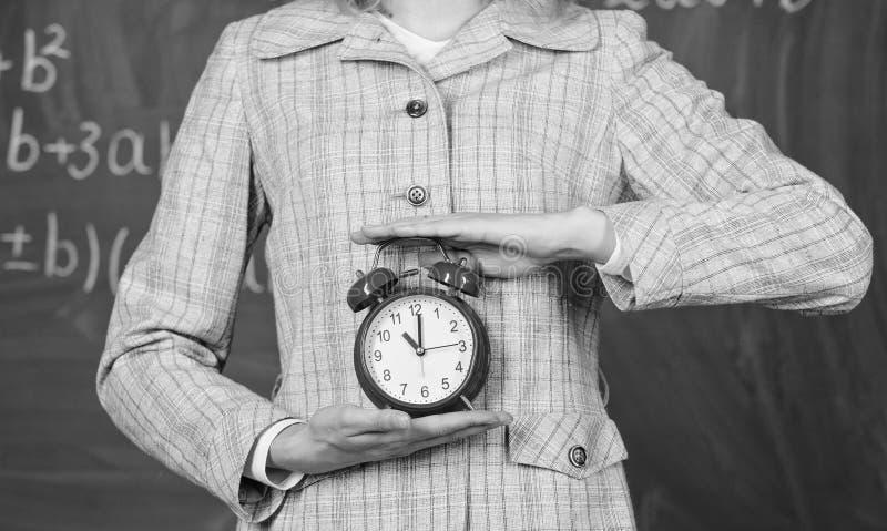 Концепция дисциплины школы План-график и режим Будильник в женских руках закрывает вверх Атрибуты учителей Большой колокол обеспе стоковые фото