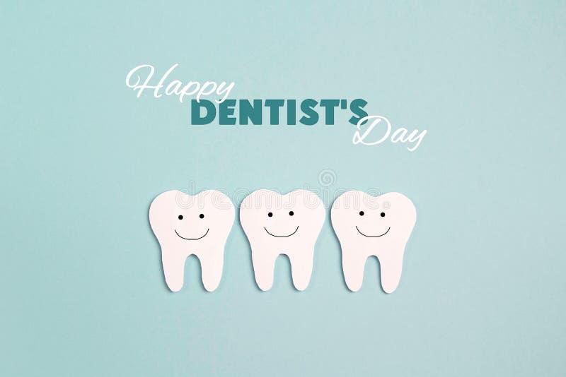 Концепция дня дантиста с зубами белой бумаги на голубой предпосылке стоковое фото rf