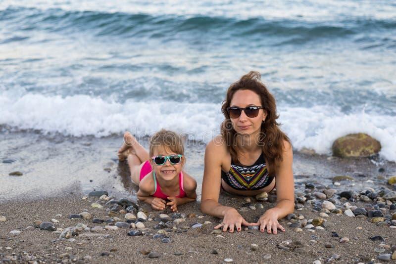 Концепция семейного отдыха: мама и дочь на пляже стоковая фотография rf