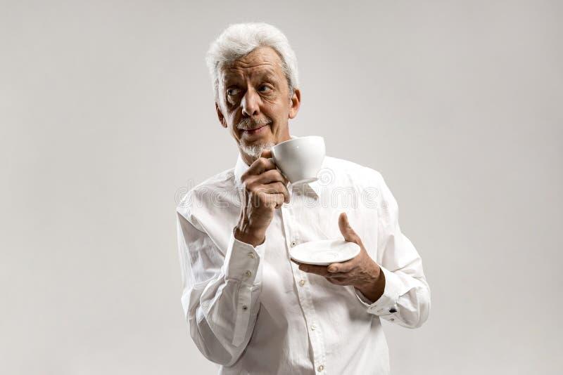 Концепция старости, питья и людей - счастливый старший человек с чашкой чаю дома стоковые изображения rf