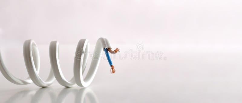 Концепция электричества со спиральным кабелем на отраженной предпосылке таблицы белой стоковое фото rf