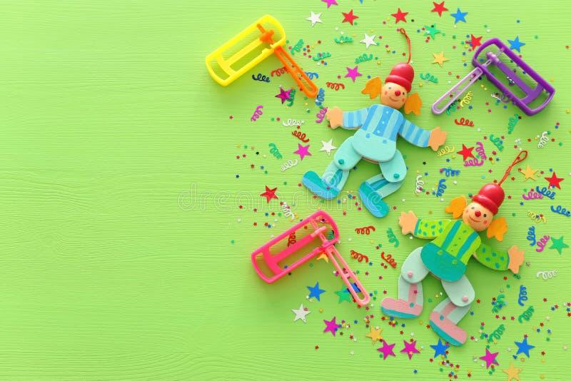 Концепция торжества Purim & x28; еврейское holiday& x29 масленицы; , клоуны, confetti и noisemaker над деревянной зеленой предпос стоковые изображения rf