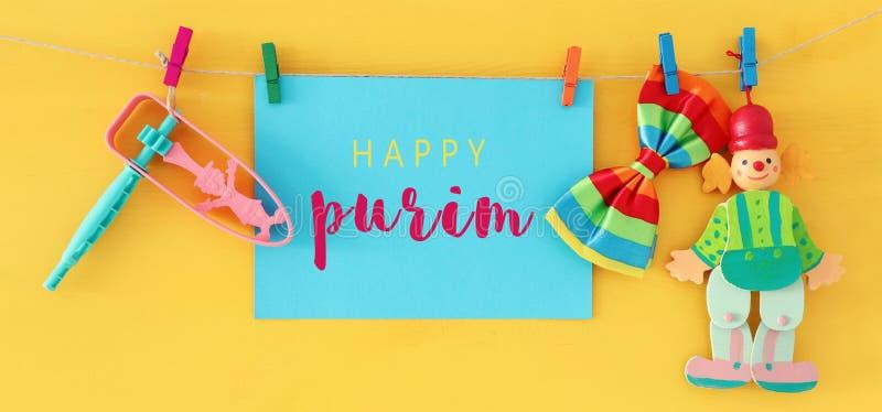 Концепция торжества Purim & x28; еврейское holiday& x29 масленицы; с примечанием, клоуном и noisemaker над деревянной желтой пред стоковые фото
