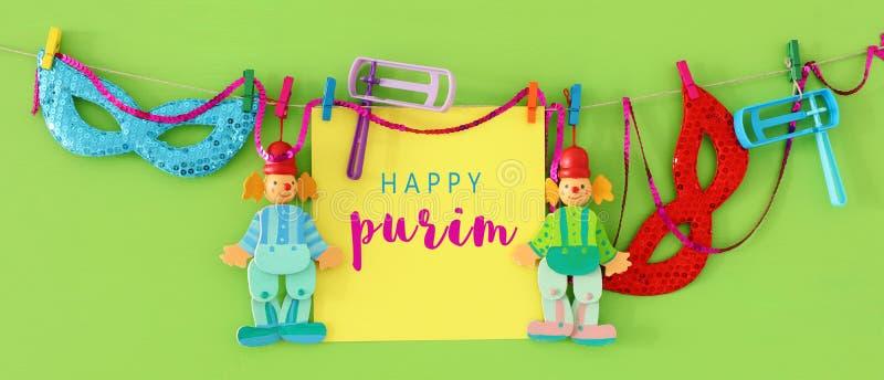 Концепция торжества Purim & x28; еврейское holiday& x29 масленицы; с примечанием, клоуном и noisemaker над деревянной зеленой пре стоковое изображение rf
