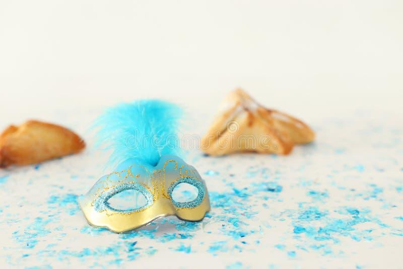 Концепция торжества Purim & x28; еврейское holiday& x29 масленицы; Традиционный hamantaschen печенья с маской над белым деревянны стоковое изображение rf