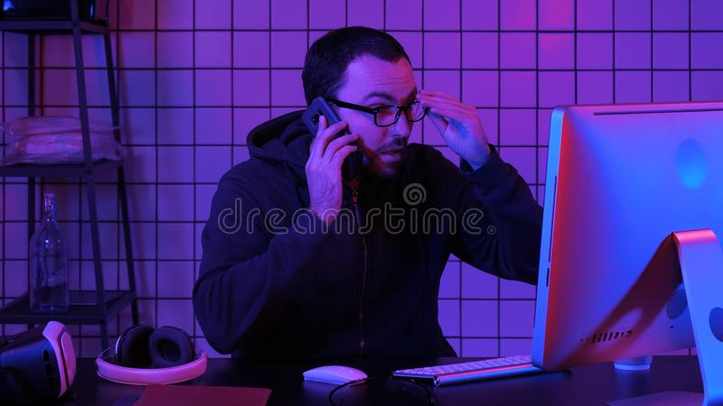 Кодирующ специалиста в случайном с компьютером и говорящ по телефону пока кодирующ информацию для создания удобного программного  стоковое фото