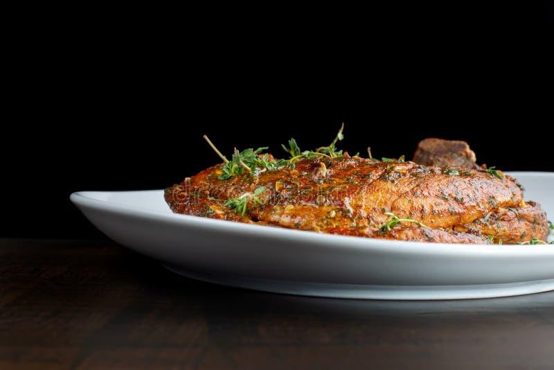 Костяшка свинины жаркого на белой плите, взбрызнутой с розмариновым маслом стоковое изображение