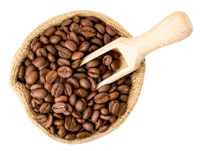 Кофейные зерна в сумке и деревянной ложке на белом Форма верхней части стоковая фотография rf