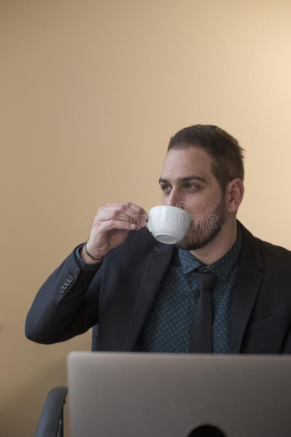 кофе бизнесмена выпивая работая на ноутбуке в офисе принимая примечания стоковая фотография rf