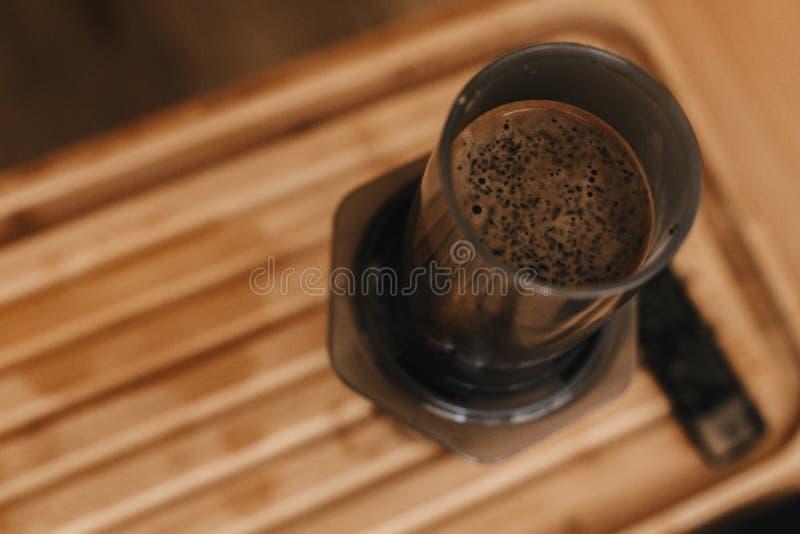 Кофе зацветая в aeropress близко вверх, альтернативный метод заваривать кофе Aeropress и стеклянная чашка на деревянном столе, вз стоковое фото rf
