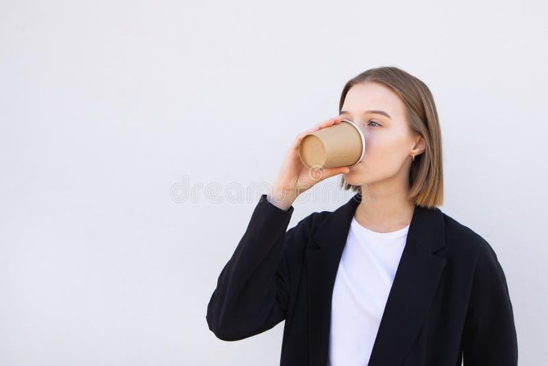Кофе привлекательной молодой женщины дела выпивая от бумажного стаканчика на белой предпосылке стоковое изображение