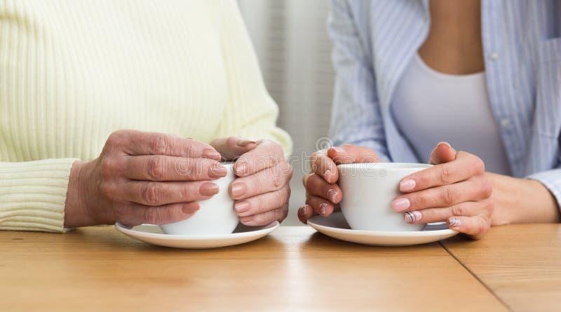 Кофе дочери и старшей матери выпивая, крупный план стоковое изображение