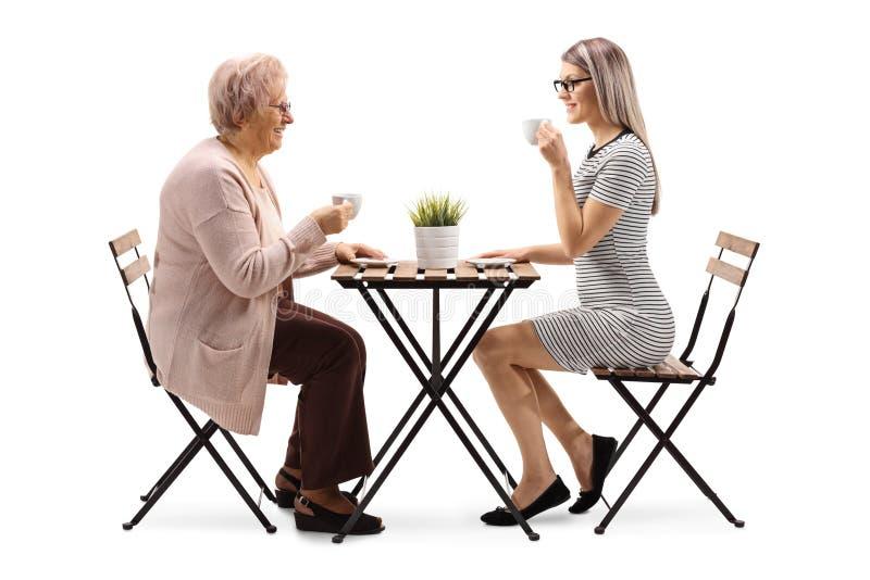 Кофе старшей женщины выпивая с молодой женщиной на таблице стоковые фотографии rf