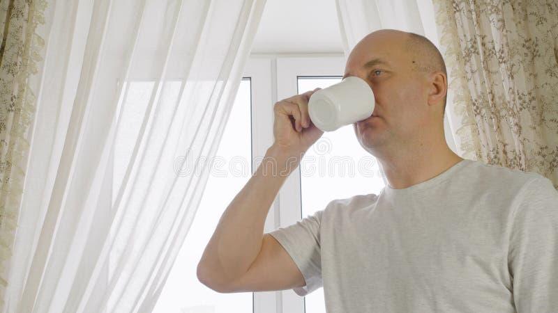 Кофе утра взрослого человека выпивая на уютной кухне на предпосылке окна Человек портрета жизнерадостный наслаждаясь горячим чаем стоковое фото