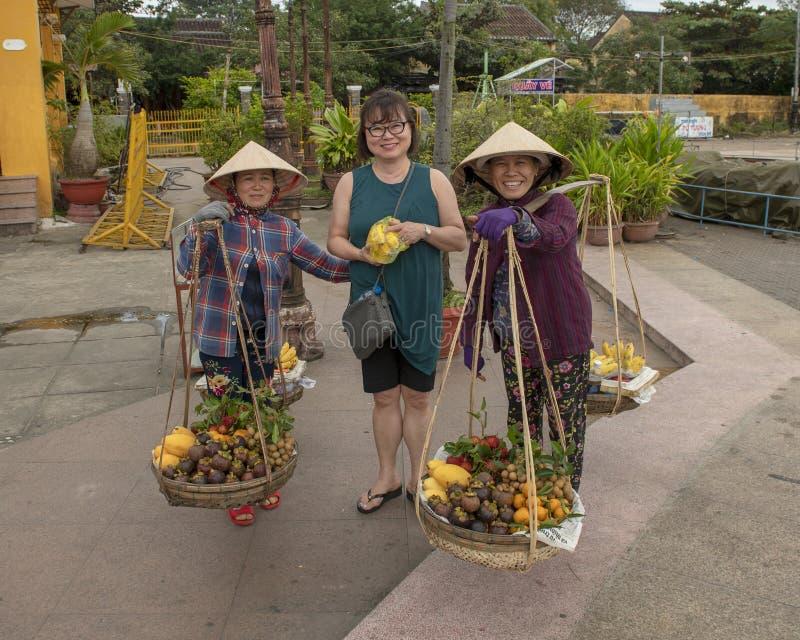 Корейский турист с классическими въетнамскими уличными торговцами продающ плод в Hoi, Вьетнаме стоковое изображение