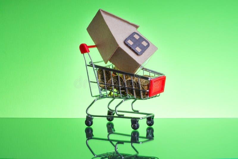 Корзина, монетки и коробка дома на зеленой предпосылке стоковые изображения rf