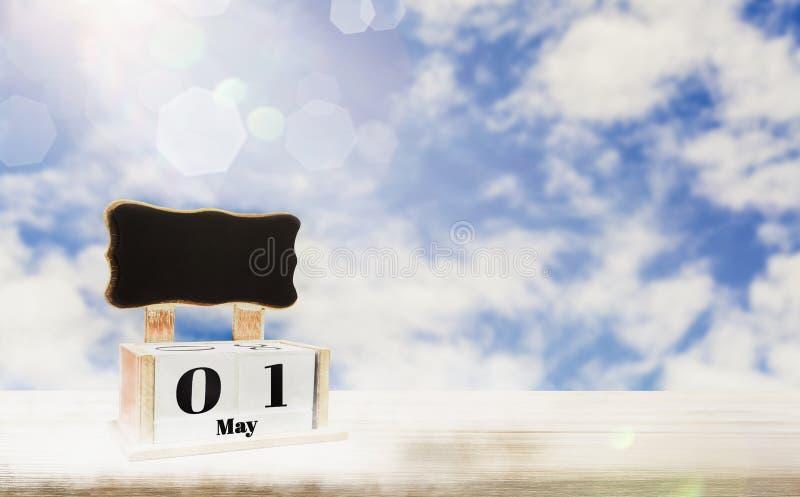 Коробка календаря с классн классным для входя в текста, дней 1-ое мая устанавливает на деревянном столе, яркой предпосылке голубо стоковые фото
