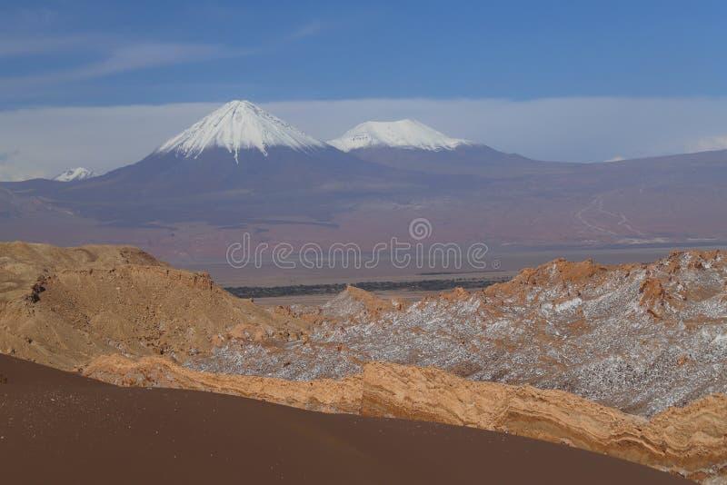 Ла луна ( Valle de; Долина Moon) и покрытые снег вулканы, пустыня Atacama, Чили стоковое фото rf